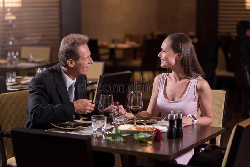 Prettig paar die in het restaurant communiceren royalty-vrije stock afbeeldingen
