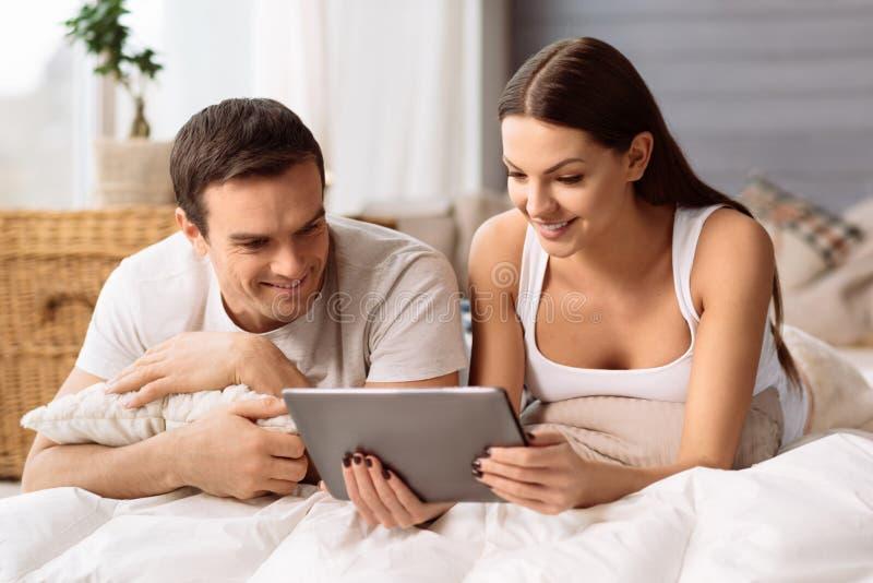 Prettig positief paar die het tabletscherm bekijken royalty-vrije stock foto