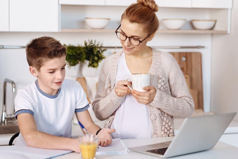 Prettig weinig jongen die huistaak met zijn moeder doen royalty-vrije stock foto's