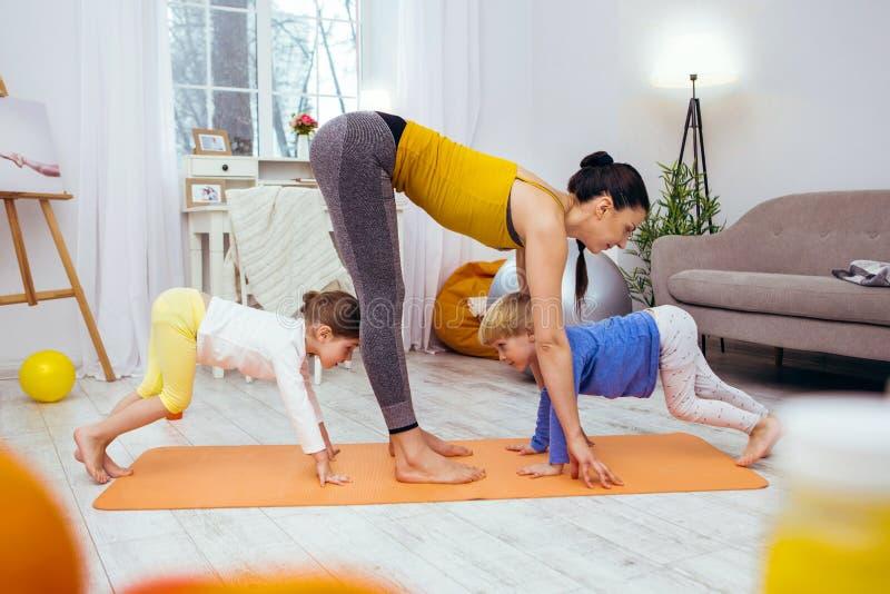 Prettige actieve kinderen die samen met hun moeder opleiden stock afbeeldingen