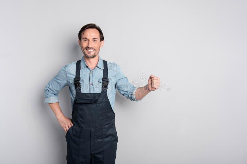 Prettige arbeider die zich tegen grijze backgound bevinden stock fotografie