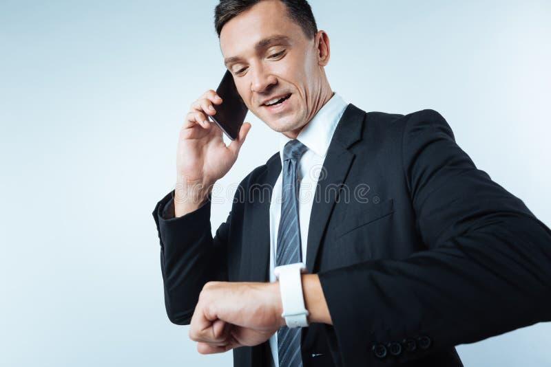Prettige bezige zakenman die zijn smartwatch bekijken stock foto