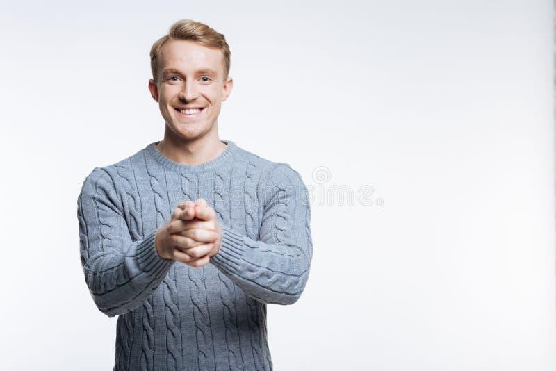 Prettige blonde mens die in sweater op camera richten stock afbeelding