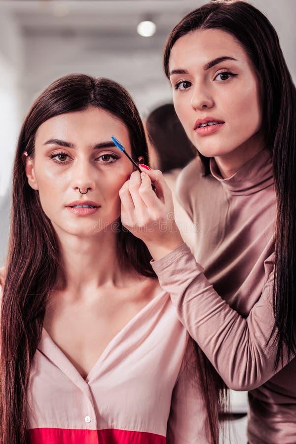 Prettige ervaren make-upkunstenaar die professioneel advies geven stock foto's