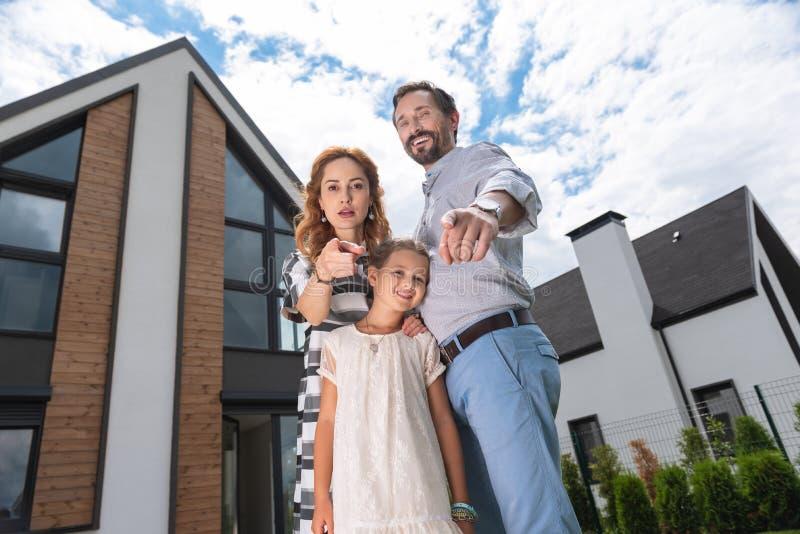Prettige gelukkige familie die zich voor hun nieuw huis bevinden royalty-vrije stock afbeeldingen