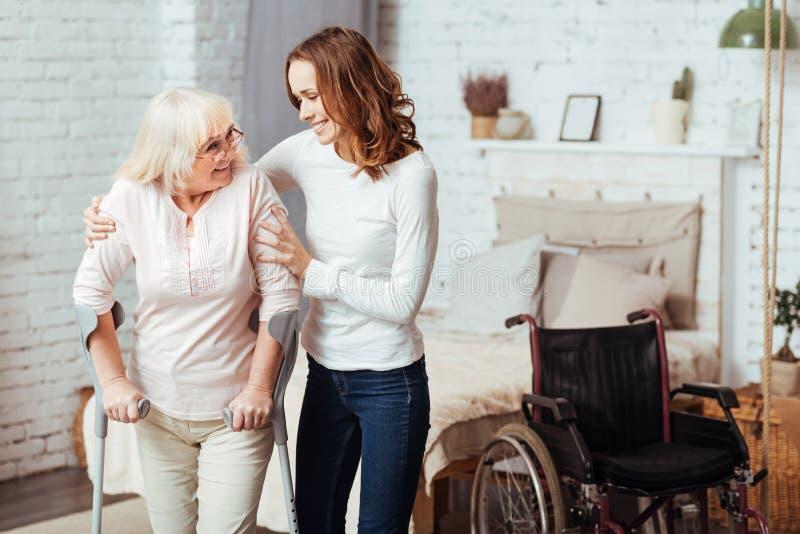 Prettige gevende vrouw die met rehabilitatie haar gehandicapte grootmoeder helpen stock fotografie