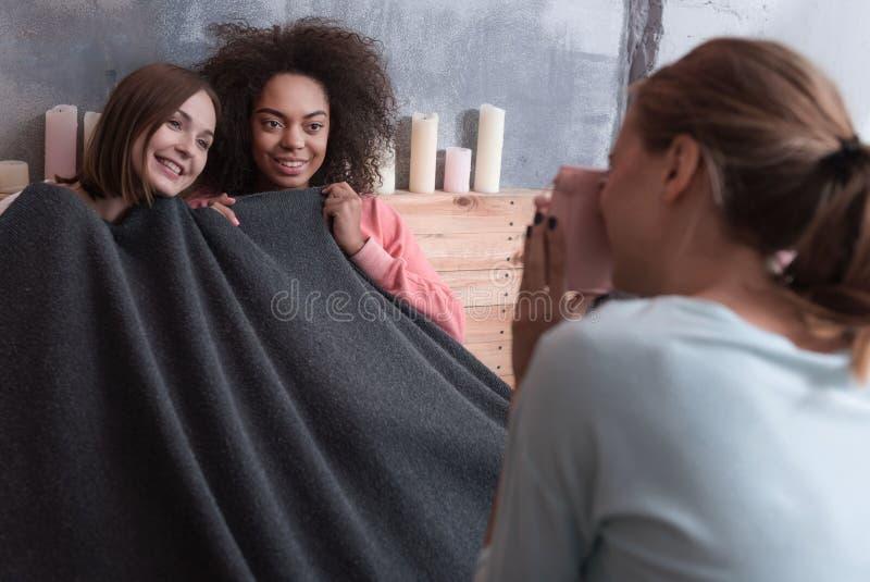 Prettige glimlachende meisjes thuis omvat met de deken stock fotografie