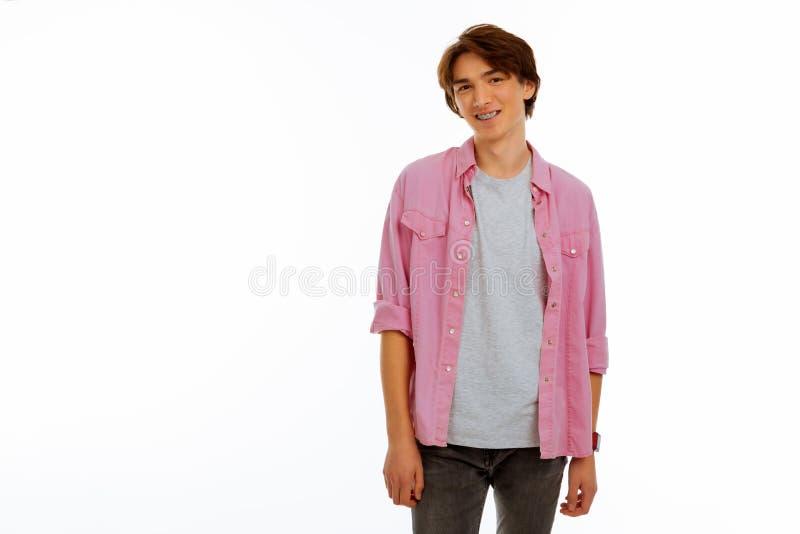 Prettige jonge mens die steunen op zijn tanden dragen stock foto
