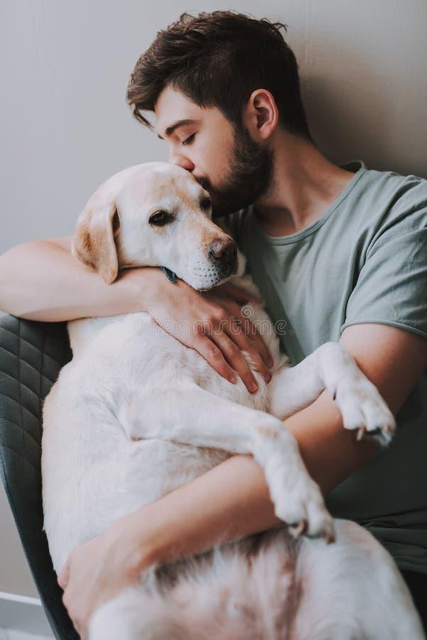 Prettige jonge mens die zijn hond kussen terwijl het uitdrukken van liefde stock foto