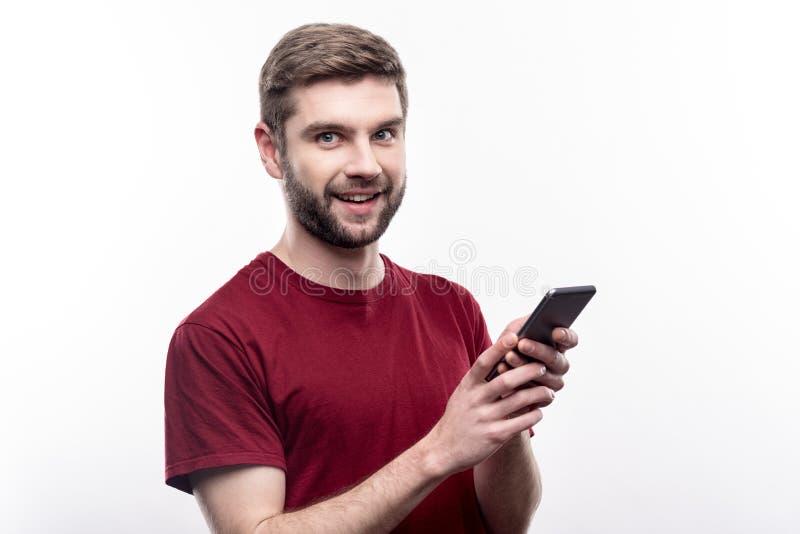 Prettige jonge mens die zijn vrienden en het stellen texting stock afbeeldingen