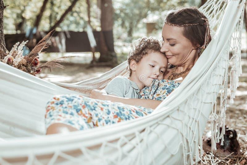 Prettige jonge moeder die met haar zon rusten royalty-vrije stock afbeeldingen