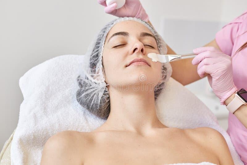Prettige jonge vrouw die anti het verouderen procedure hebben Doctocr in cosmetological kliniek die appliess masker op haar cliën royalty-vrije stock foto