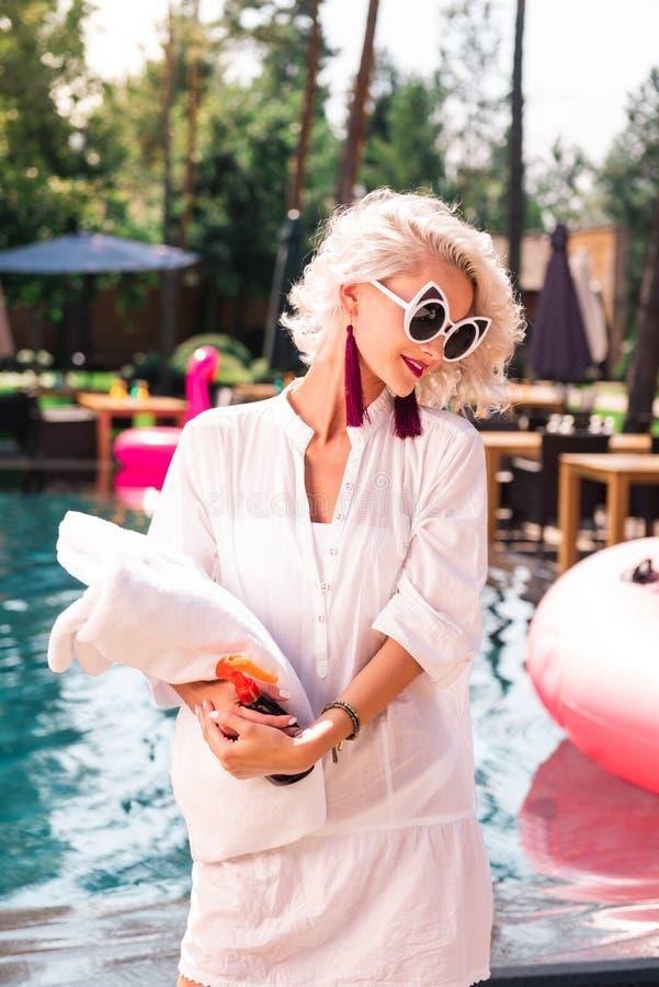 Prettige jonge vrouw die een handdoek en een zonnescherm houden stock fotografie