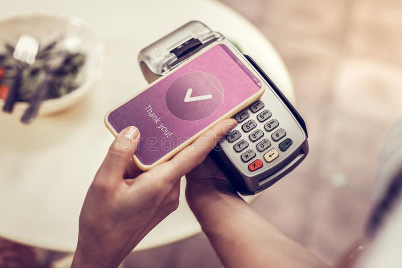Prettige jonge vrouw die haar smartphone voor betaling gebruiken royalty-vrije stock foto's
