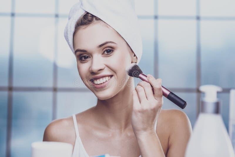 Prettige jonge vrouw die schoonheidsmiddelen toepassen stock afbeeldingen