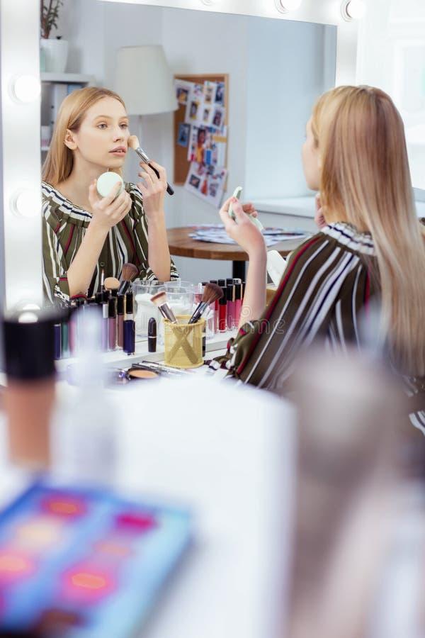 Prettige jonge vrouw die zich in de spiegel bekijkt stock foto's