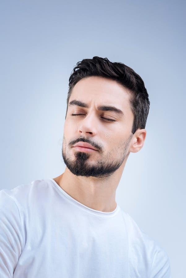 Prettige jonge zich met zijn gesloten ogen bevinden en mens die dromen stock foto's