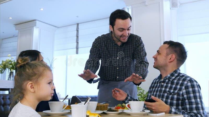Prettige kelner die aan bezoekers spreken - jonge vriendschappelijke familie die diner hebben bij restaurant stock afbeeldingen