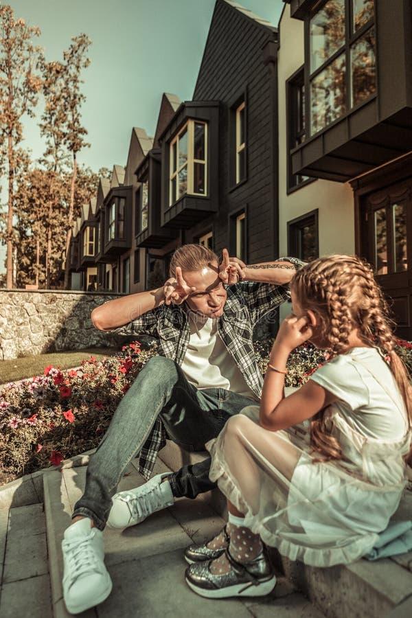 Prettige kinderachtige vader in het comfortabele uitrusting spelen met langharige dochter royalty-vrije stock afbeeldingen