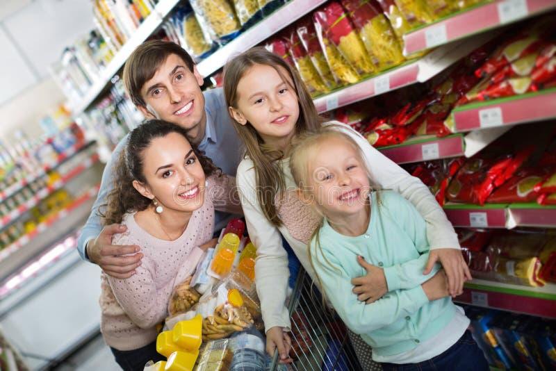 Prettige klanten met kinderen die voedsel in hypermarket kopen royalty-vrije stock foto's