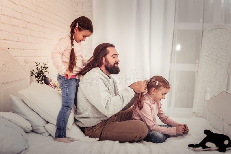 Prettige knappe mens die een vlecht voor zijn dochter doen royalty-vrije stock afbeeldingen