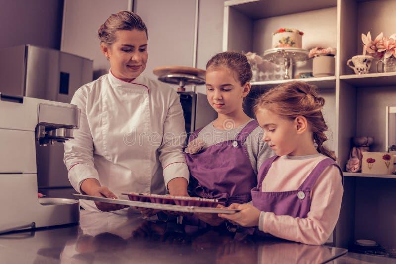 Prettige leuke meisjes die een dienblad met muffins houden stock afbeelding