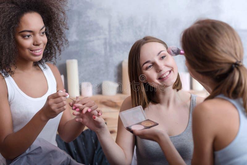 Prettige meisjes die haar vriend helpen die thuis klaar worden stock foto