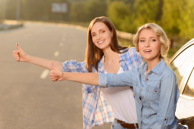 Prettige meisjes die zich dichtbij auto bevinden stock foto's