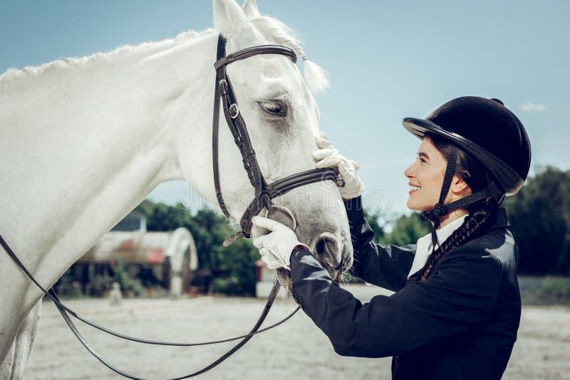 Prettige mooie vrouw die het witte paard bekijken royalty-vrije stock afbeeldingen