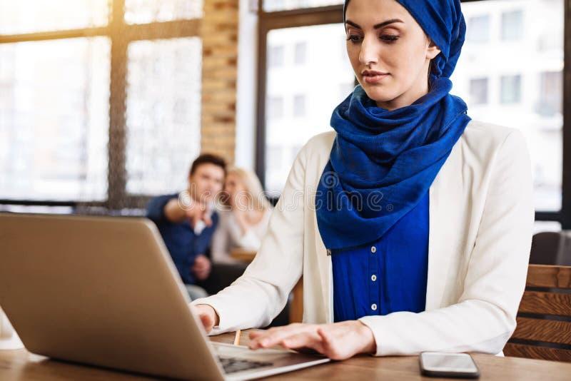 Prettige moslimonderneemster die aan laptop werken royalty-vrije stock afbeelding