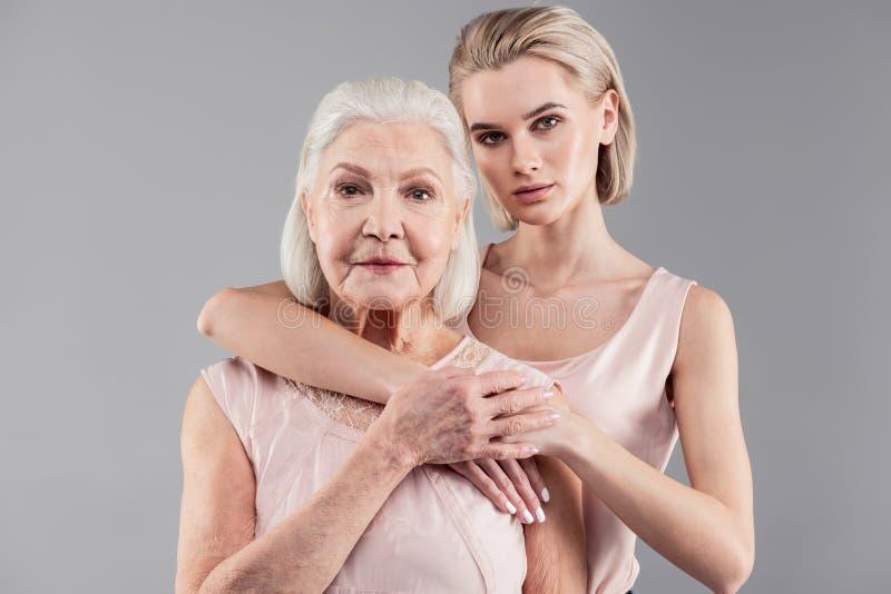 Prettige oude dame en haar aantrekkelijk blondemeisje die hun verhoudingen tonen stock afbeeldingen