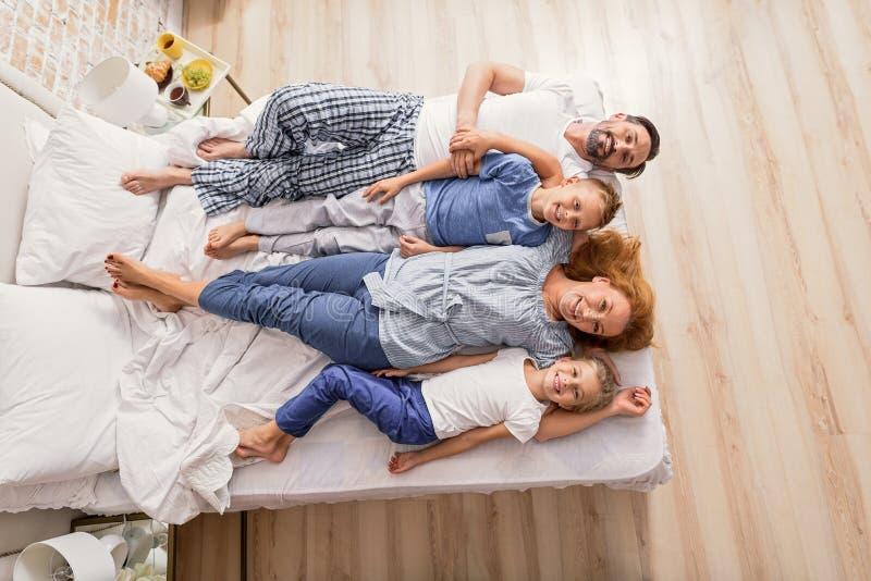 Prettige ouders met jonge geitjes in bed royalty-vrije stock foto's
