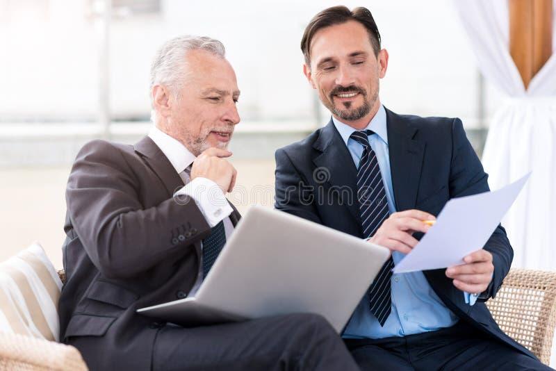 Prettige professionele collega's die op de laag zitten royalty-vrije stock afbeeldingen