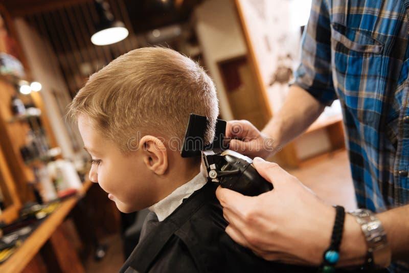 Prettige professionele kapper die haircutting machine met behulp van royalty-vrije stock afbeeldingen