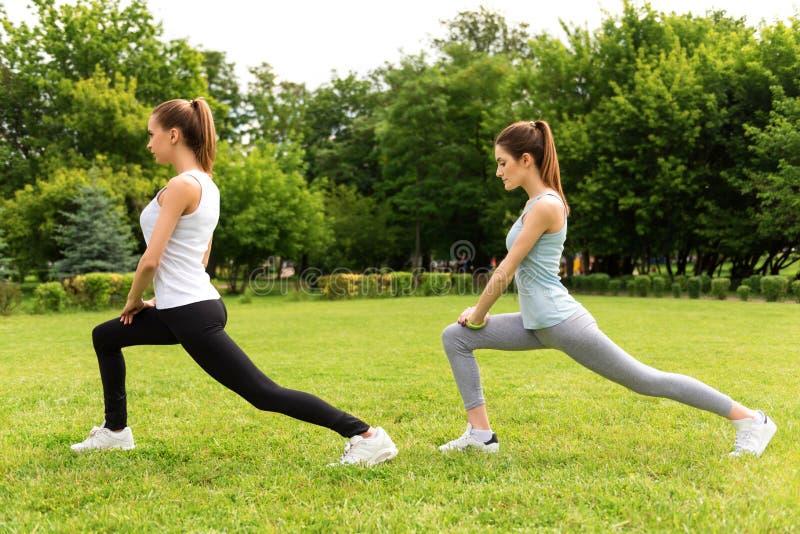 Prettige slanke vrouwen die sportoefeningen doen stock afbeelding