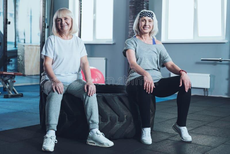 Prettige teruggetrokken dames die rust op band na opleidingsklasse hebben royalty-vrije stock foto's