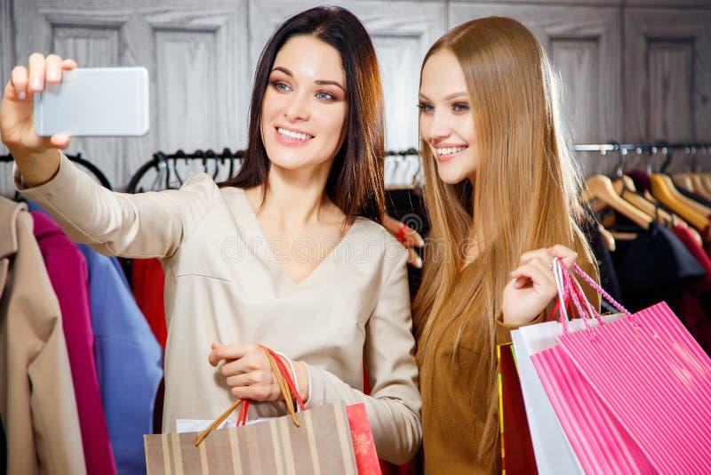Prettige tevreden jonge in een wandelgalerij winkelen en meisjes die selfie terwijl het houden van pakketten maken royalty-vrije stock afbeeldingen