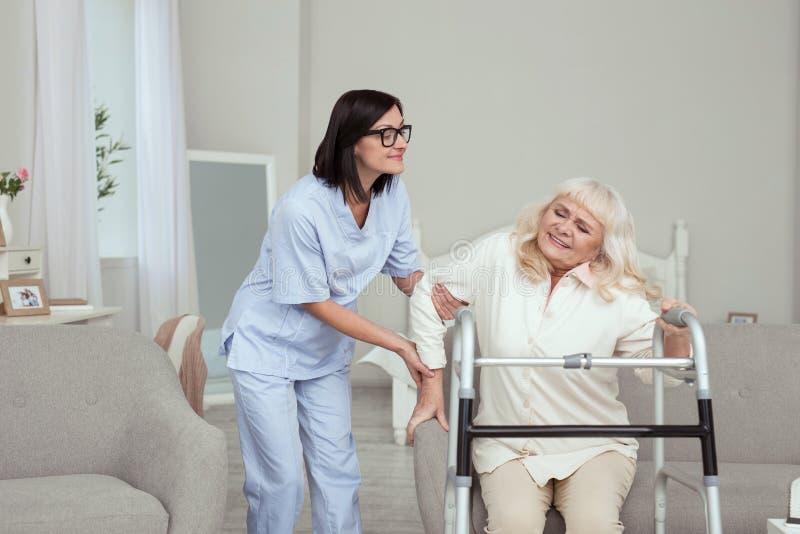 Prettige verpleegster die hulp oudere vrouw aanbieden royalty-vrije stock afbeeldingen