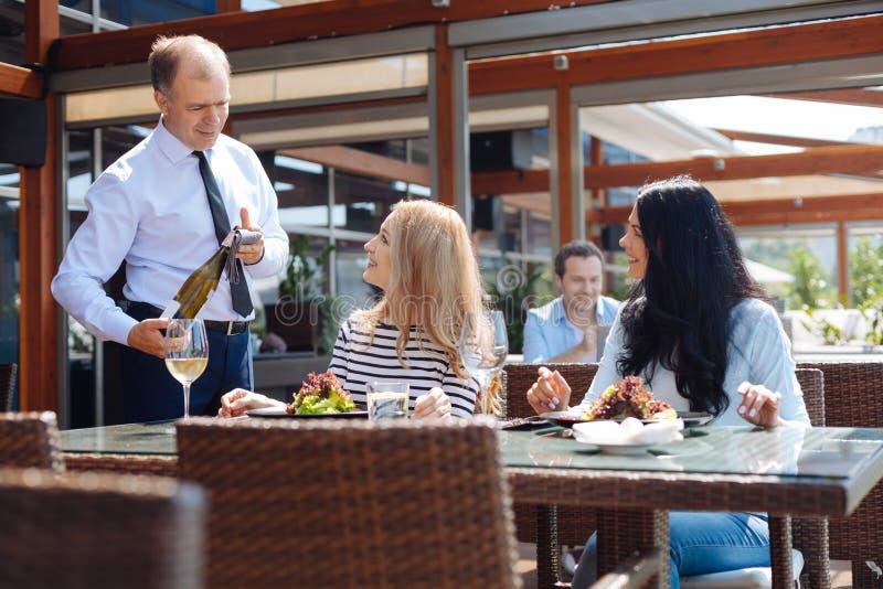 Prettige vriendschappelijke kelners dienende klanten stock afbeeldingen