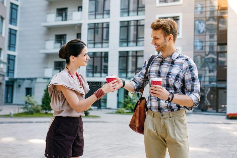 Prettige vriendschappelijke mens die een kop van koffie geven aan zijn vriend royalty-vrije stock foto