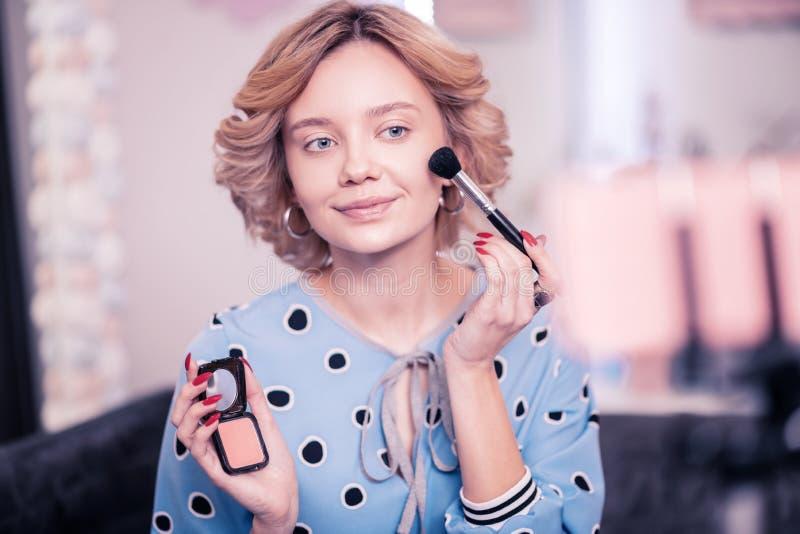 Prettige vrouw die wat gezichtspoeder zetten terwijl het doen van make-up royalty-vrije stock foto's