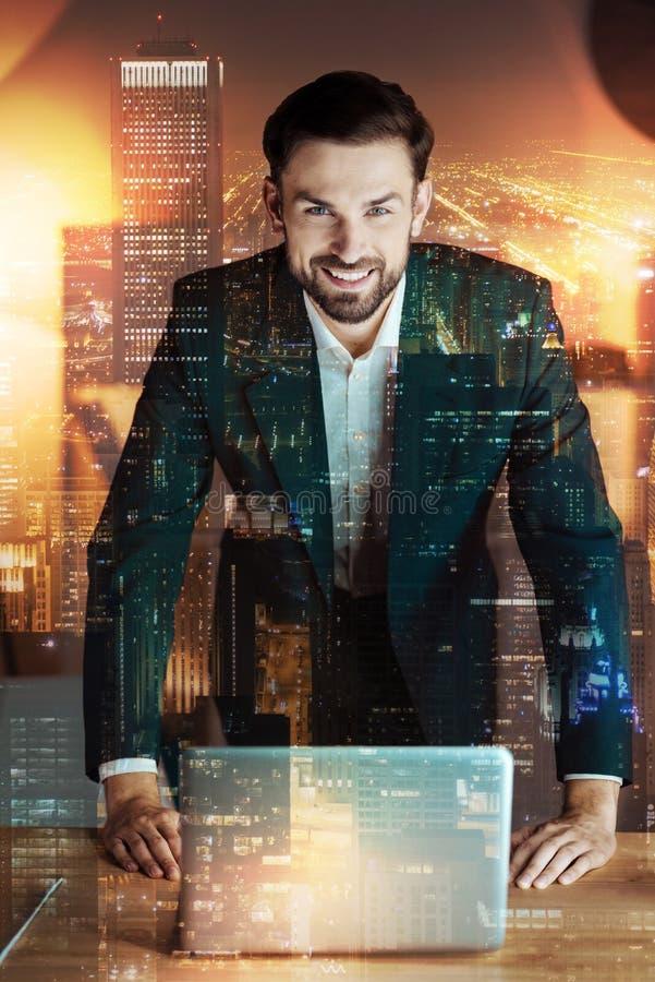 Prettige zakenman die op lijst met laptop leunen stock foto's