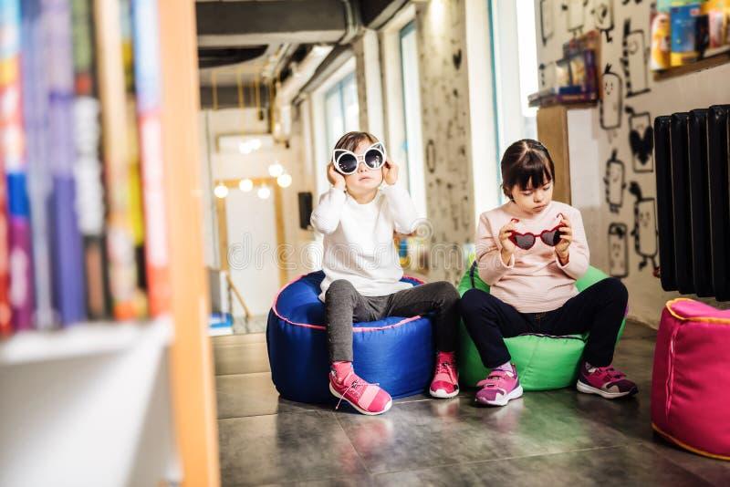 Prettige zonnige kinderen die grappige heldere zonnebril houden royalty-vrije stock afbeelding