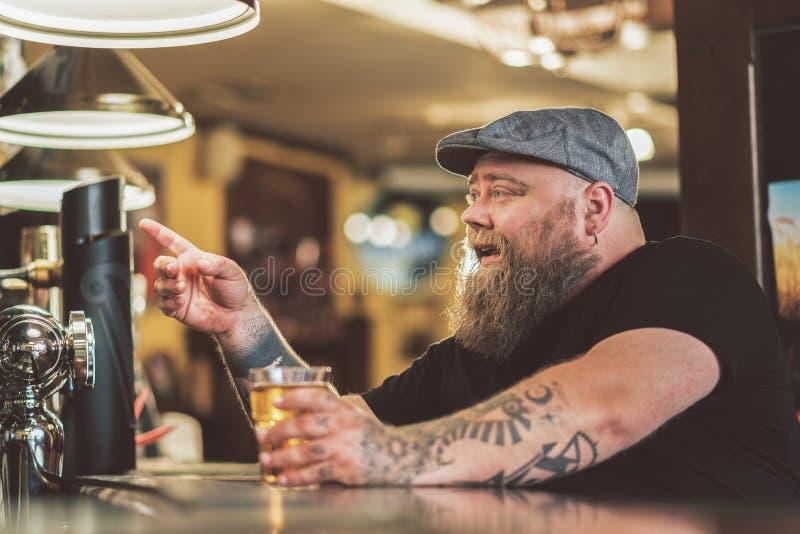 Prettige zwaarlijvige kerel die licht lagerbier in bar drinken stock foto