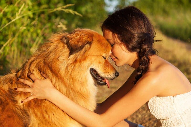 Prettty ung flicka som kramar hennes gulliga hund royaltyfri bild