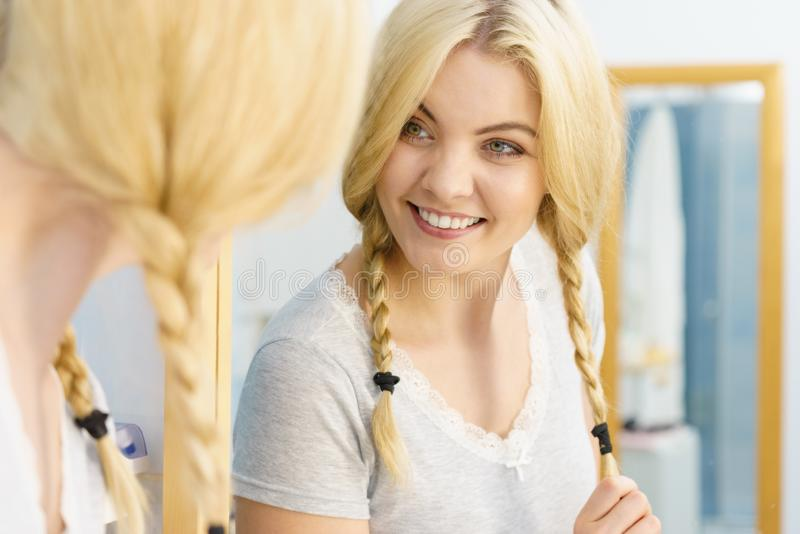 Lovely blonde woman in braids. Pretty adorable woman having two cute braids on blonde hair. Haircare and hairstyling concept royalty free stock photo