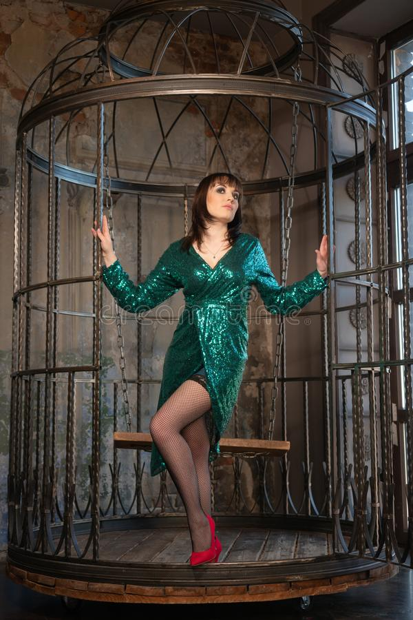 Beautiful woman sitting in a cage alone because of her limitations and complexes. adult female wearing green evening dress inside royalty free stock photo