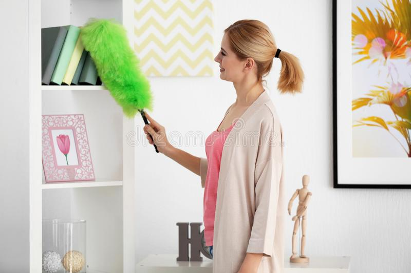 Pretty adult woman cleaning house. From dust stock photography
