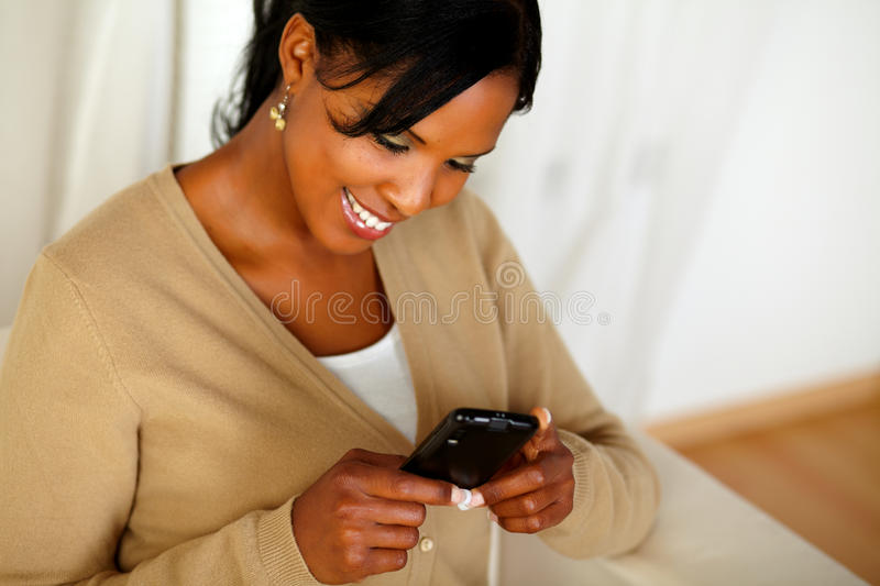 Pretty adult woman reading a message on cellphone royalty free stock images