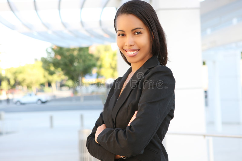 Pretty African American Business Woman. A pretty african american business woman at her office building royalty free stock image